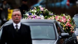 De rouwstoet met de kist van Ximena komt aan bij het crematorium. Tussen de bloemen ligt een rugbybal.